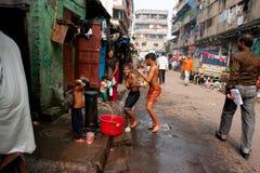 Barn hoppar på gatan på badtiden Arkivbild