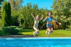 Barn hoppar till simbassängvatten och har gyckel, ungar på familjsemester Arkivbild
