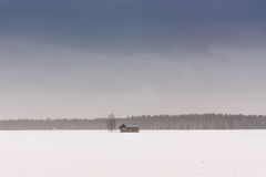 Barn Houses In The Spring Fields 3. The spring is coming and the snow is slowly melting away. The sadness of the lonely barn houses is emphasized by the stock photo