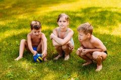 Barn i baddräkter sitter på grönt gräs i sommar fotografering för bildbyråer