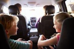 Barn i baksäte av bilen på resa med föräldrar Fotografering för Bildbyråer