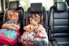 Barn i bilen går till skolan, lyckliga söta framsidor av systrar arkivfoton