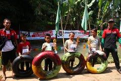 Barn i byn spelar gladlynta vattenglidbanor på floden, royaltyfri bild