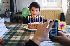 Barn i dagen av hans nionde födelsedag som blåser stearinljusen på th Arkivbilder