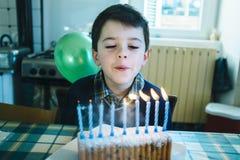 Barn i dagen av hans nionde födelsedag som blåser stearinljusen på th Arkivbild