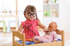Barn i dagis Unge i daghem Liten flickaförskolebarn som spelar doktorn med dockan arkivbilder