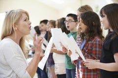 Barn i den sjungande gruppen som uppmuntras av läraren arkivbilder