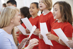 Barn i den sjungande gruppen som uppmuntras av läraren Royaltyfria Bilder