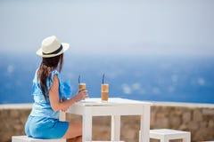 Barn i det utomhus- kafét som tycker om havssikt Den härliga kvinnan kopplar av under exotisk semester på stranden som tycker om  Arkivbilder