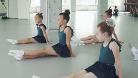 Barn i en danskurs små flickor sitter på golvet och upprepar förehavanden bak läraren lager videofilmer