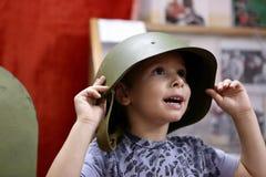 Barn i en militär hjälm Fotografering för Bildbyråer