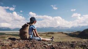 Barn i en vandring lite är flickan vila, och att beundra sikten av bergen som sitter på, vaggar liten turist arkivfilmer