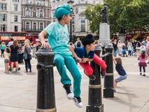 Barn i färgrik kläder spelar på järnräcke i Trafalgar Royaltyfri Foto