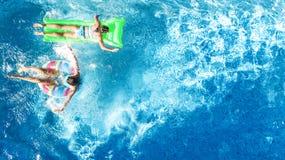 Barn i för surrsikt för simbassäng flyg- fom över, lyckliga ungar simmar på den uppblåsbara cirkelmunken, och madrassen, flickor  arkivbilder