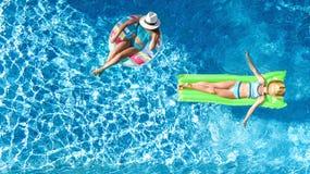 Barn i för surrsikt för simbassäng flyg- fom över, lyckliga ungar simmar på den uppblåsbara cirkelmunken, och madrassen, flickor  royaltyfri bild