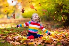 Barn i fallpark Unge med höstsidor Fotografering för Bildbyråer