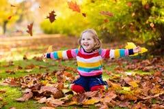 Barn i fallpark Unge med höstsidor Royaltyfri Bild