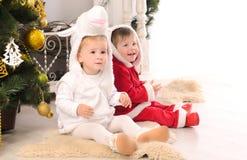 Barn i festliga dresser på julträdet royaltyfri bild