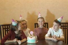 Barn i festliga hattar spelar och har gyckel på en children& x27; s-parti royaltyfria bilder
