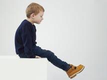 Barn i gula kängor Dana ungar Barn pyssammanträde på en kub royaltyfria bilder