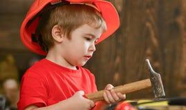 Barn, i gulligt spela för hjälm som byggmästare eller reparatör, att reparera eller handcrafting Att bulta för ungepojke spikar i royaltyfria bilder