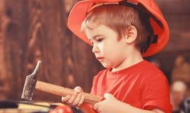 Barn, i gulligt spela för hjälm som byggmästare eller reparatör, att reparera eller handcrafting Att bulta för ungepojke spikar i royaltyfri bild