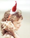 Barn i jultomtenhatt på stranden Royaltyfri Bild