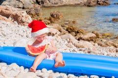 Barn i jultomtenhatt på stranden Arkivbild