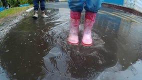Barn i kängor som går och hoppar i lerig pöl efter regn arkivfilmer