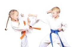 Barn i karategi slår sparkar och handen Arkivbild