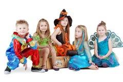 Barn i karnevaldräkter sitter på bröstkorg Fotografering för Bildbyråer