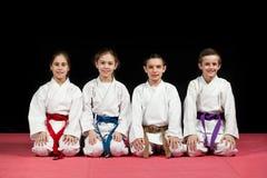 Barn i kimonosammanträde på tatami på kampsportseminarium Selektivt fokusera Arkivfoto