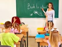 Barn i klassrum med läraren Arkivbilder
