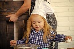 Barn i kockhatten som bryter ägget av bunken i kök royaltyfria foton