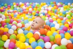 Barn i kulöra bollar Fotografering för Bildbyråer