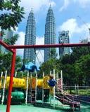 Barn i lekplatsen och Petronas tvillingbröder KL royaltyfri foto