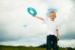 Barn i lekplatsunge i handlingpojken som spelar med frisbeen Fotografering för Bildbyråer