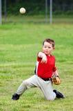 Barn i likformig som kastar baseball Arkivfoto
