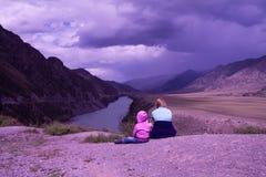 Barn i lila kläder sitter i berg under den molniga vioen Arkivbild