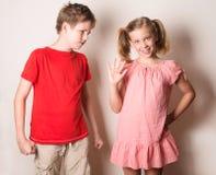 Barn i olika lynnen Systern som retar hennes broder, fejkar sm Royaltyfri Bild