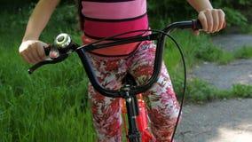 Barn i parkera på en cykel Liten flicka med en cykel Idrotts- barn i natur stock video