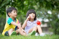 Barn i parkera som blåser såpbubblor Royaltyfria Foton