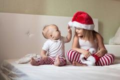 Barn i pyjamas och jullock som spelar på sängen Royaltyfri Foto