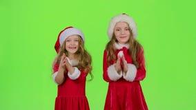Barn i röda hattar för nytt år håller ögonen på en saga i teatern och applåderar deras händer grön skärm arkivfilmer