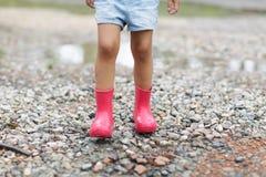 Barn i rosa gummistöveler i regnet som hoppar i pölar Ungen som spelar i sommar, parkerar Utomhus- gyckel vid n?got v?der royaltyfri bild