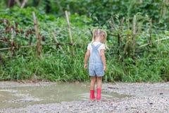 Barn i rosa gummist?veler i regnet som hoppar i p?lar Ungen som spelar i sommar, parkerar Utomhus- gyckel vid n?got v?der royaltyfri bild