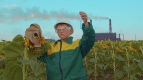 Barn i skyddande maskering med växtsolrosen på bakgrundsindustrianläggningen ekologisk milj?fotof?rorening f?r kris stock video