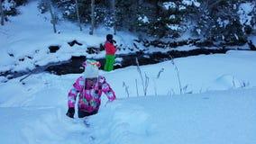 Barn i snö vid liten vik royaltyfri bild