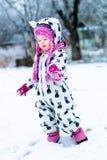 Barn i snöig dag Behandla som ett barn flickan i vit snowsuite, och rosa färghatten, kängahandskar i snövintern parkerar Royaltyfri Foto