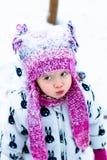 Barn i snöig dag Behandla som ett barn flickan i vit snowsuite, och rosa färghatten, kängahandskar i snövintern parkerar Arkivfoto